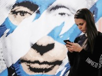 A woman looks at a mobile phone as she stands in front of a painting depicting Russian president Vladimir Putin at the 'SUPERPUTIN' exhibition in UMAM museum in Moscow