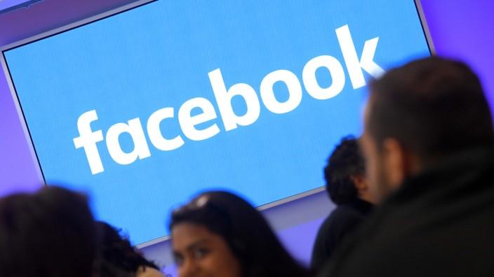 Menschen vor dem Facebook-Logo