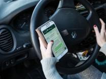 Frau am Steuer schreibt eine SMS Handy im Auto *** Woman at Tax writes a SMS Handy in Car