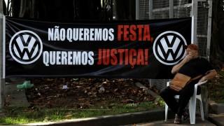 Former Volkswagen worker Raimundo Nonato sits in front of VW factory headquarters in Sao Bernardo do Campo