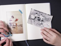 Two people sticking old fotographs in album model released Symbolfoto PUBLICATIONxINxGERxSUIxAUTxHUN