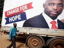 A supporter of George Weah listens to the announcement of the presidential election results on the radio, in Monrovia, Liberia
