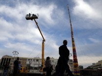 People walk past workers on a crane during the assembling of the last parts of a 36-meter (118 feet) tower, in an attempt to break the Guinness world record for the highest building blocks structure in Tel Aviv