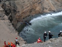 Rescue workers  and police work at the scene after a bus crashed with a truck and careened off a cliff along a sharply curving highway north of Lima
