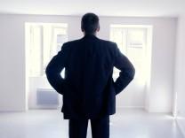 Mann in einer leeren Wohnung Wohnungssuche Eigentumswohnung iblbej01655322