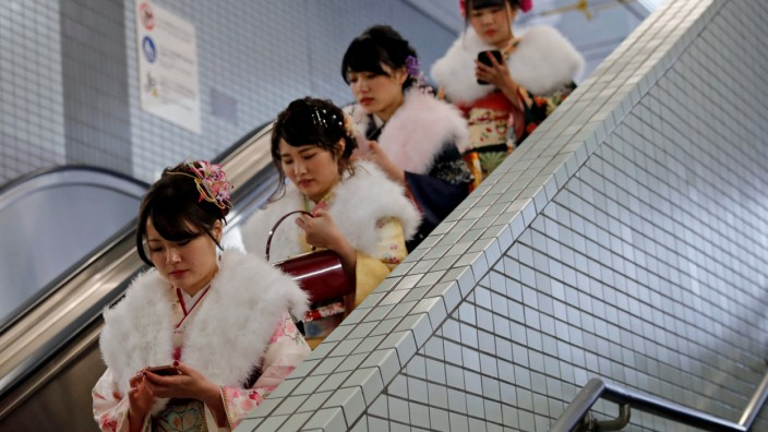 Japanese women wearing kimonos ride an escalator at a subway station after attending their Coming of Age Day celebration ceremony in Tokyo