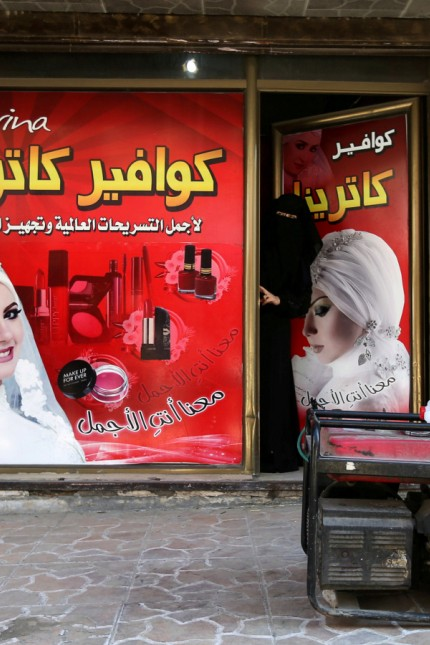 A Palestinian woman looks out of a hairstyle salon as a generator is seen outside in the southern Gaza Strip