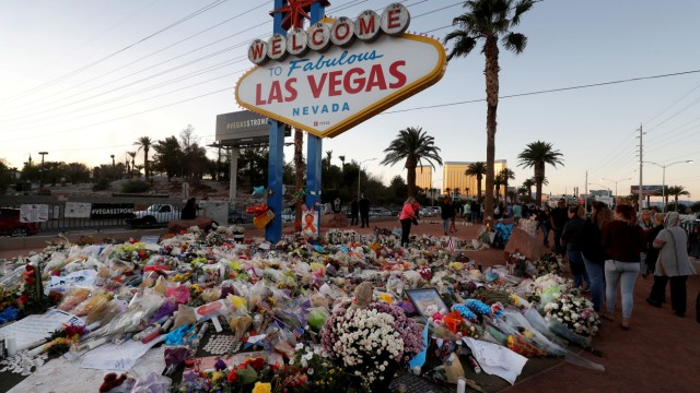The 'Welcome to Las Vegas' sign is surrounded by flowers and items, left after the October 1 mass shooting, in Las Vegas