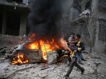 Syria Civil Defence member carries a wounded child in Hamoria, Eastern Ghouta, Damascus