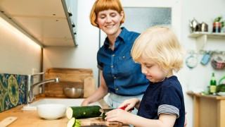 Littel boy chopping vegetables in the kitchen while his mother watching him model released Symbolfot