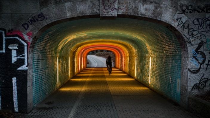 München: Au-Haidhausen, Schmuckfoto, Symbolfoto: Regenbogentunnel an der Isar, Radfahrer.