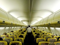 A cabin crew member serves passengers onboard a Ryanair passenger aircraft travelling from Madrid International Airport to Bergamo Airport