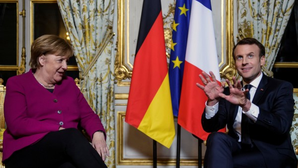 French President Emmanuel Macron and German Chancellor Angela Merkel react during their meeting at Elysee Palace in Paris