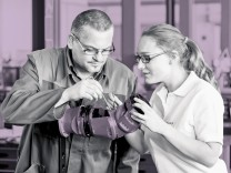 Ein Ausbilder erklärt einer Auszubildenden zur Mechatronikerin Montagearbeiten an einer Roboterhand