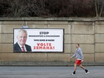 A man walks past a poster promoting the incumbent president Milos Zeman in Prague