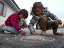 Children of migrants use chalk while playing in refugee deportation registry centre in Manching
