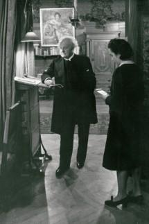 Gerhart Hauptmann am Stehpult mit Annie Pollak, Stenogrammblock in den Händen