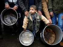 A Palestinian boy holds cooking pots during a protest against aid cuts, outside United Nations' offices in Gaza City