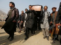 Afghan men carry the coffin of one of the victims of yesterday's car bomb attack at in Kabul