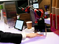 A man scans a QR code printed on a ticket used to order a coffee from the robot barista called 'Sawyer' during its demonstration at 'Henn-na Cafe,' meaning 'Strange Cafe' in Japanese
