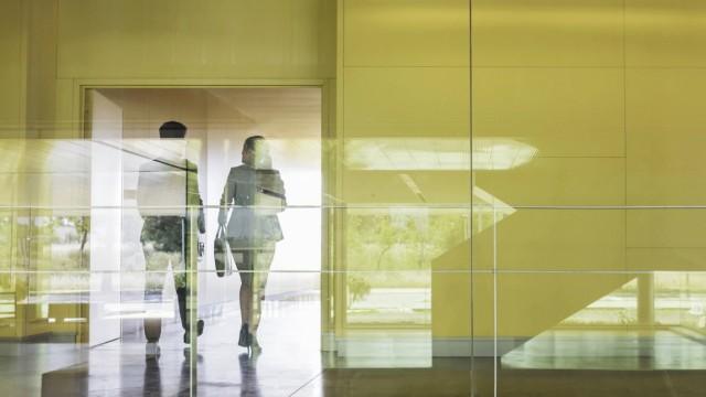 Business people walking in modern office corridor Business people walking in modern office corridor