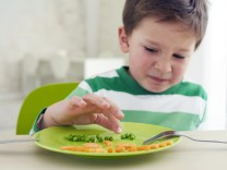 Germany Munich Boy eating peas and carrots showing anthropomorphic face model released property r