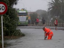 Emergency personnel work on a flooded road in Nelson, after the downgraded Tropical Cyclone Fehi brought heavy rain in New Zealand