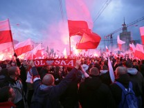 Protesters carry Polish flags and National Radical Camp flags during a rally, organised by far-right, nationalist groups, to mark 99th anniversary of Polish independence in Warsaw