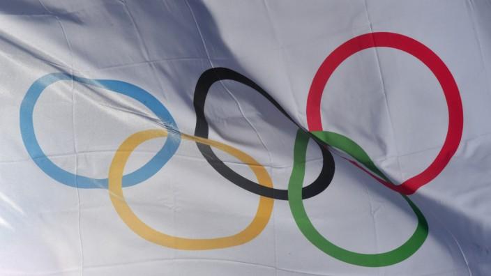 Eine Flagge mit den Olympischen Ringen weht im Wind