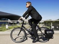 Ein Geschäftsmann düst mit seinemPedelec durch München.