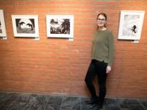 Ricarda Reimann vor der Ausstellung Behind|Art, die sie mit Künstlern aus der Pfennigparade erarbeitet hat. Mit Arbeiten im Rathaus Unterföhring.