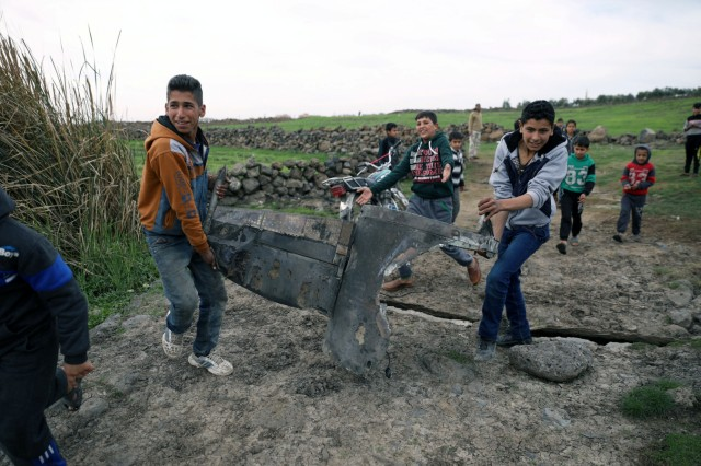 Children carry a part of a missile in Quneitra