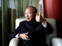 Chairman of HNA Group Chen Feng gestures during an interview in Dalian