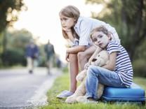 Two girls sitting on suitcase at the roadside model released Symbolfoto PUBLICATIONxINxGERxSUIxAUTxH