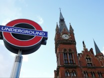 The St Pancras clock tower is seen by an Underground tube sign, London