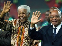 Former South African President Nelson Mandela and deputy President Jacob Zuma waves to soccer fans in Johannesburg