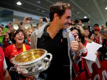 Switzerland's Federer holds his Australian Open trophy upon his arrival at Zurich Airport