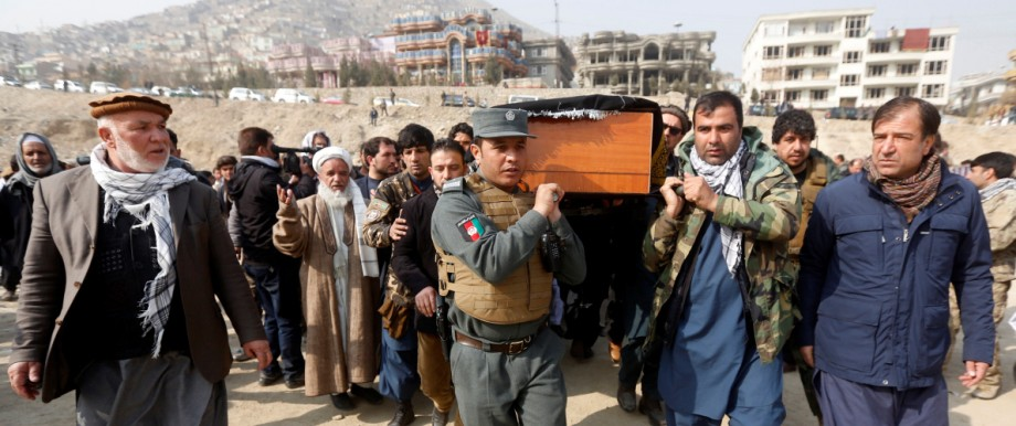 Afghan men carry the coffin of one of the victims of yesterday's car bomb attack in Kabul, Afghanistan