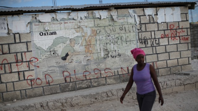 A woman walks past an Oxfam sign in Corail, a camp for displaced people of the 2010 earthquake, on the outskirts of Port-au-Prince