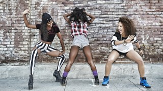 Women posing on city street