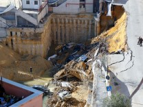 Cars are seen in a large sinkhole on a street in Rome