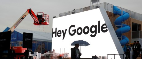 A man walks through light rain in front of the Hey Google booth under construction at the Las Vegas Convention Center in preparation for the 2018 CES in Las Vegas