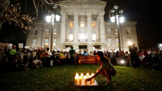 A high school student places a candle representing one of the victims of the shooting at Marjory Stoneman Douglas High School outside the North Carolina State Capitol building during a demonstration calling for safer gun laws, in Raleigh