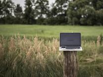 Bei einer Illustration zum Thema Internet auf dem Land steht ein Laptop mit einem Smartphone auf e