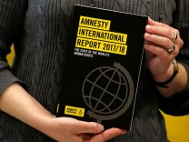 A copy of the Amnesty International Report 2017/18 is shown at a news conference in Hong Kong