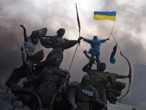 An anti-government protester waves the national flag from the top of a statue during clashes with riot police in the Independence Square in Kiev