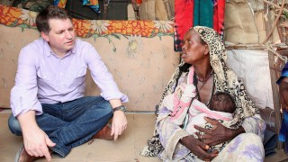 FILE PHOTO: Forsyth, Chief Executive of Save the Children UK, talks to internally displaced Somalis at a camp in Hodan district of Somalia's capital Mogadishu