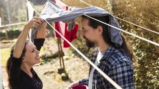 Playful couple hanging up laundry model released Symbolfoto PUBLICATIONxINxGERxSUIxAUTxHUNxONLY MIDF