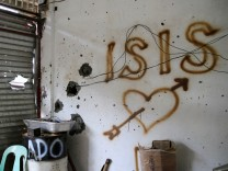 Graffiti is seen at a damaged house in Mapandi village after intense fighting between soldiers and pro-IS militant group in southern Philippines