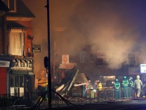 Members of the emergency services work at the site of an explosion which destroyed a convenience store and a home in Leicester
